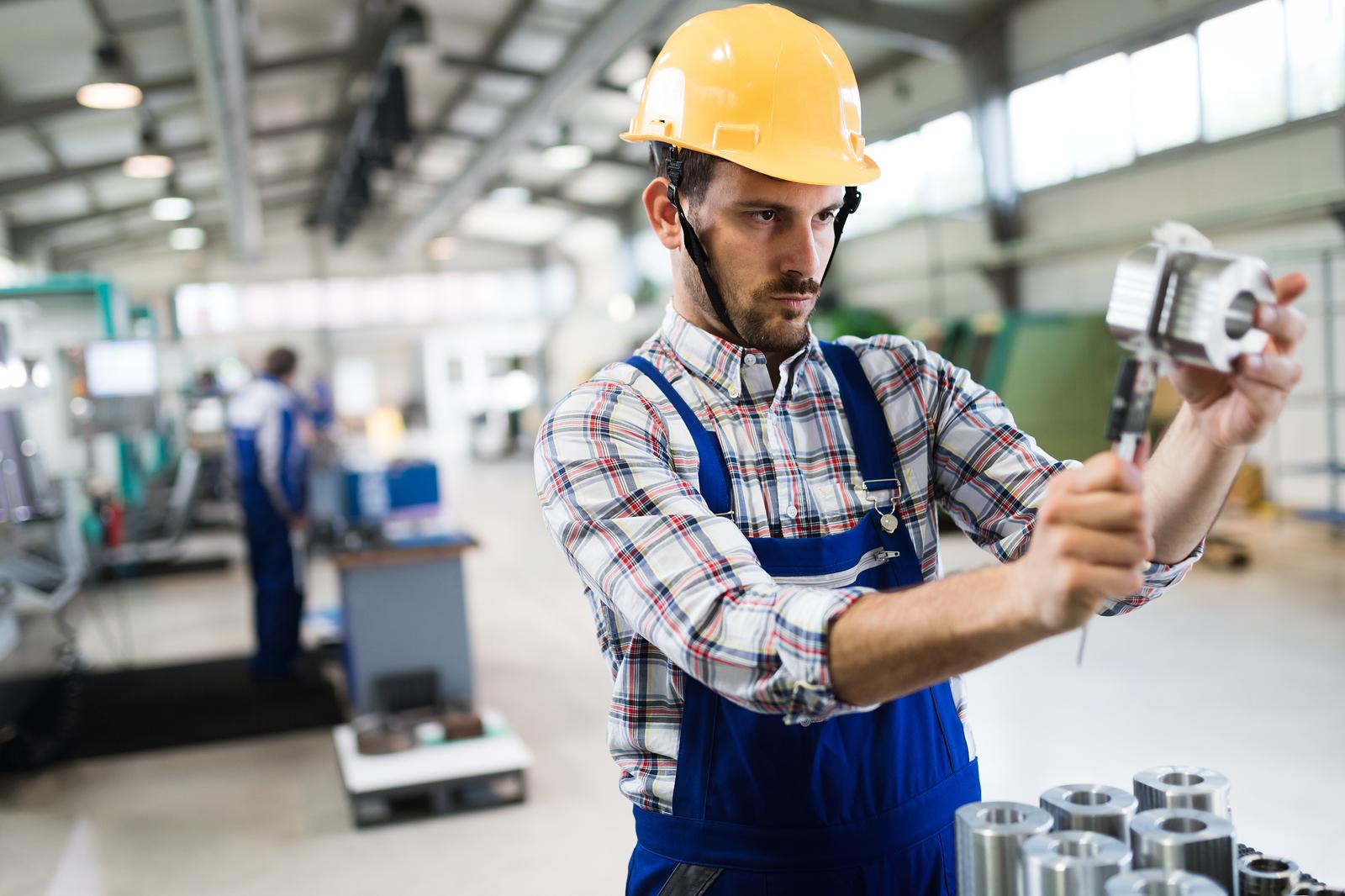 modern industrial machine operator working in metal industry factory